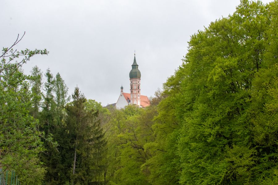 The Andechs church steeple peeks out over the treetops.