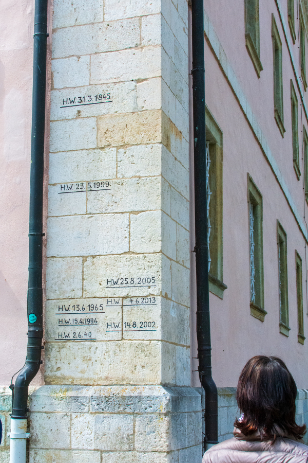 Lines on a wall show high water parks for different dates at Kloster Weltenburg.