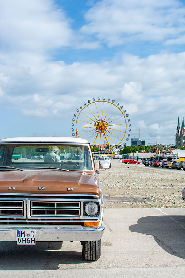 A Ford pick up truck on show at the ACM Oldtimer-Treffen with the Munich Frühlingsfest Ferris wheel in the background.