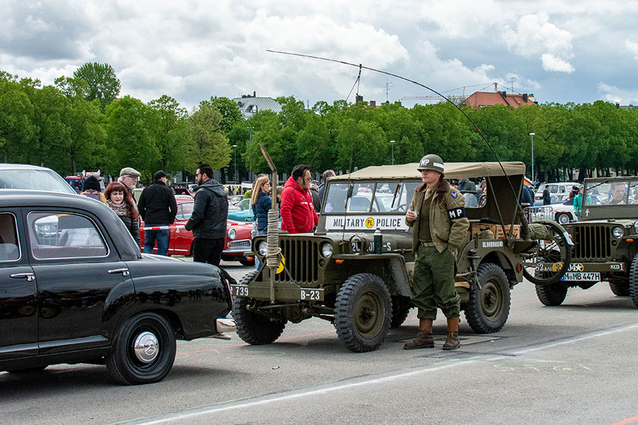 A man dressed as a military policeman stands outside of his military Jeep on the Wiesn at a Classic Car Show.