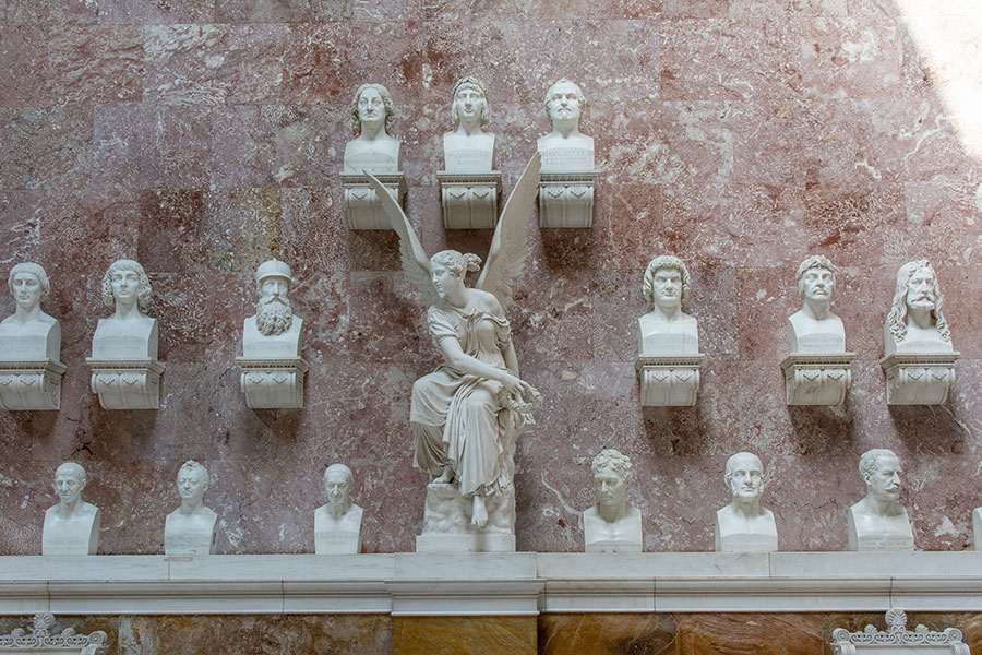 A wall of busts honoring famous Germans and an angel sit along a wall inside of Walhalla.