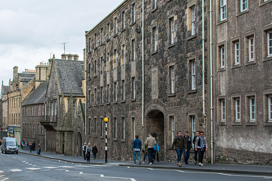 Pedestrians walk along the historic stone buildings of the Royal Mile towards Scottish Parliament and Holyrood Palace.