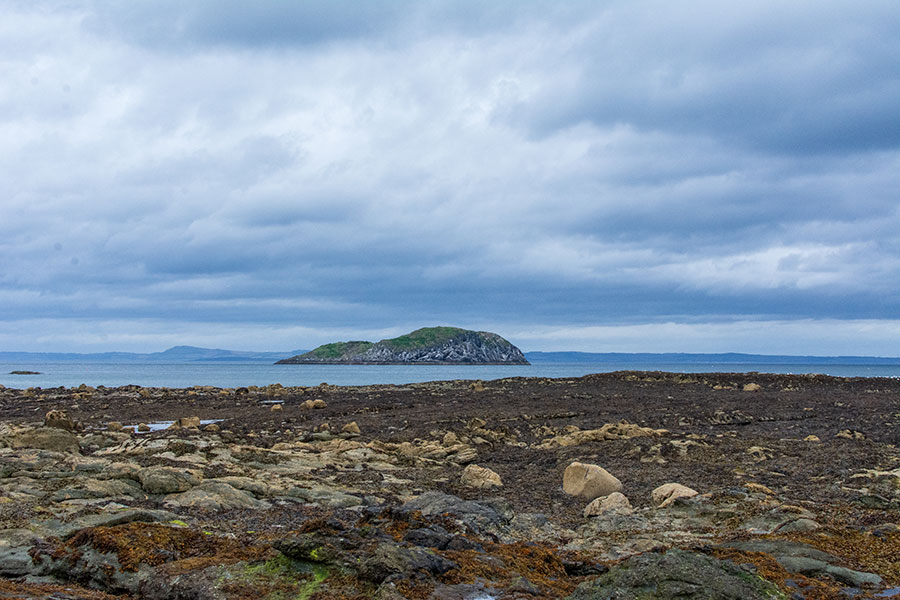 An island sits in the Firth of Forth in front of a stony beach in East Lothian.