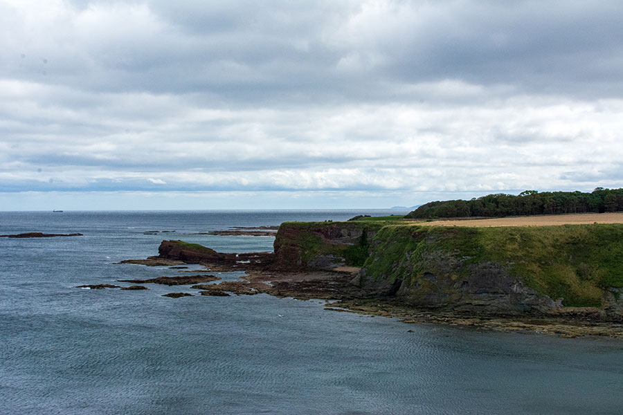 A cliff juts out into the bay in East Lothian, Scotland.