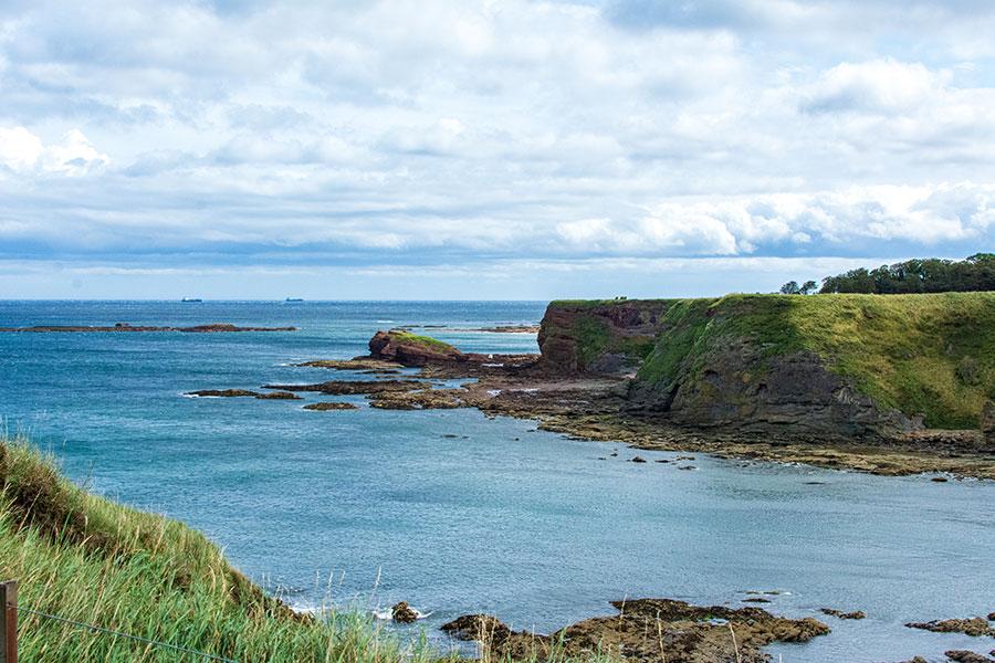 The green cliffs jut into Oxroad Bay in North Berwick, East Lothian, Scotland.