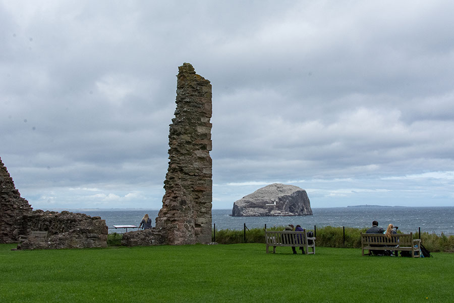 Visitors sit on benches in the courtyard at Tantallon Castle, looking onto Bass Rock, near the remains of its curtain wall.