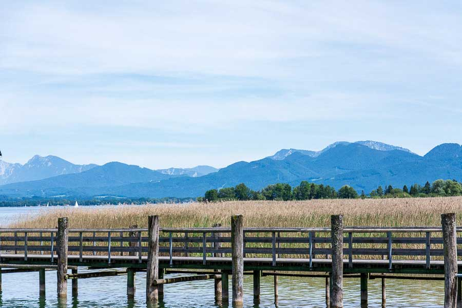 The Chiemgau Alps visible in the distance of the dock along the Chiemsee lake.