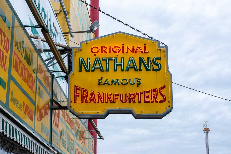 The neon sign hanging outside of Nathan's Famous original shop in Coney Island, NYC.