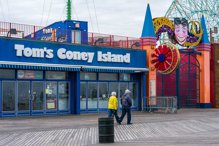 A couple walk by Tom's on the Coney Island boardwalk.