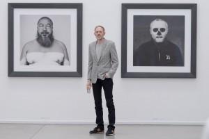 Der Fotograf Anton Corbijn in der Bochumer Ausstellung - zwischen seinen Porträts von Ai Wei Wei (links) und Damien Hirst. (Foto: © Lutz Leitmann/Presseamt der Stadt Bochum)