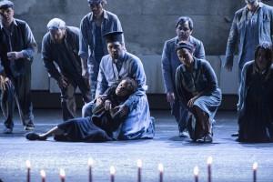 Priester Fotis (Baurzhan Anderzhanov) versucht einer Frau zu helfen, die am Ende ihrer Kräfte ist (Foto: Matthias Jung, Aalto-Theater)