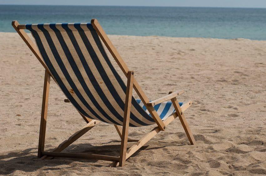 Imagem mostra uma cadeira de praia com estrutura de madeira na beira do mar.