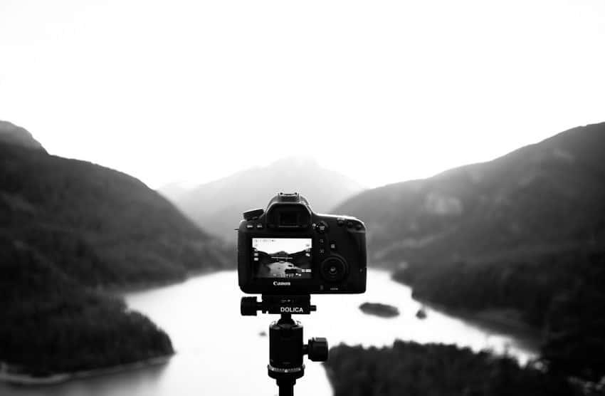 Imagem mostra uma câmera montada em um tripé fotografando uma paisagem.