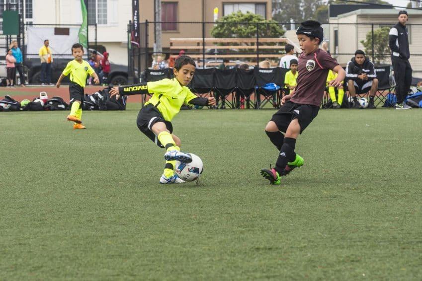 Jovem jogador de uniforme amarelo dribla adversário em uma partida de futebol entre crianças.