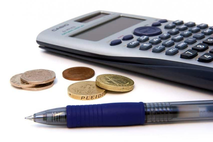 Imagem mostra uma calculadora científica ao lado de algumas moedas e de uma caneta azul.