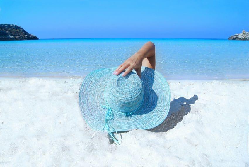 Imagem mostra mulher com chapéu azul deitada em frente ao mar.
