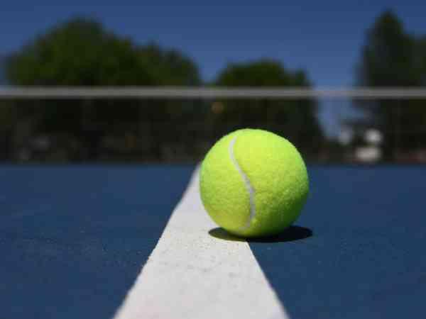 Bola de tênis no chão azul de uma quadra.