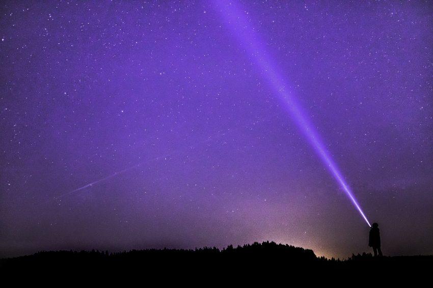 Imagem da natureza à noite com uma pessoa ao fundo e uma lanterna ligada iluminando.