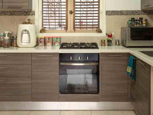 Forno embutido em armário da cozinha, na bancada está instalado um cooktop.