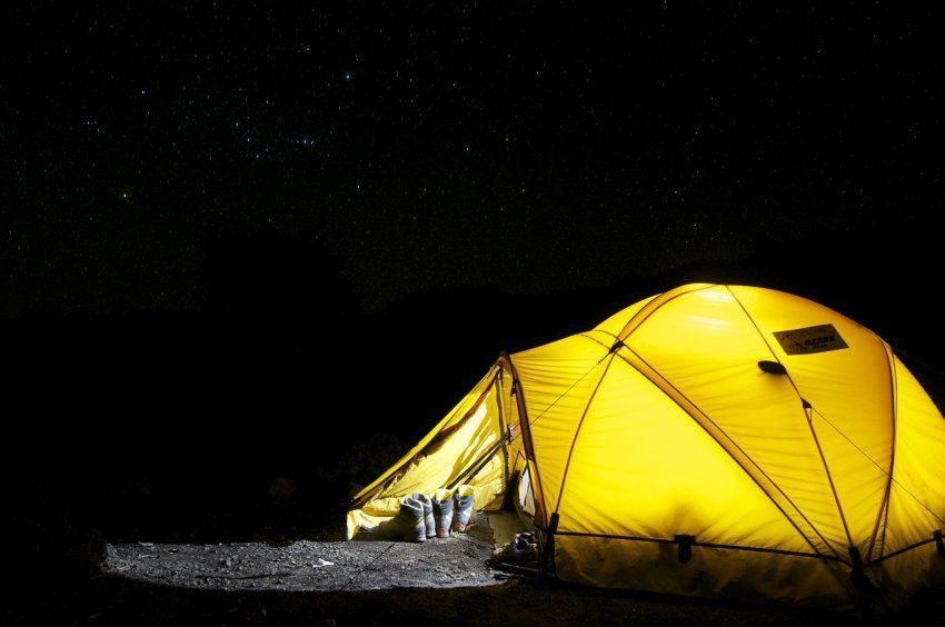 Barraca de acampamento na escuridão, sendo iluminada internamente por uma lanterna.