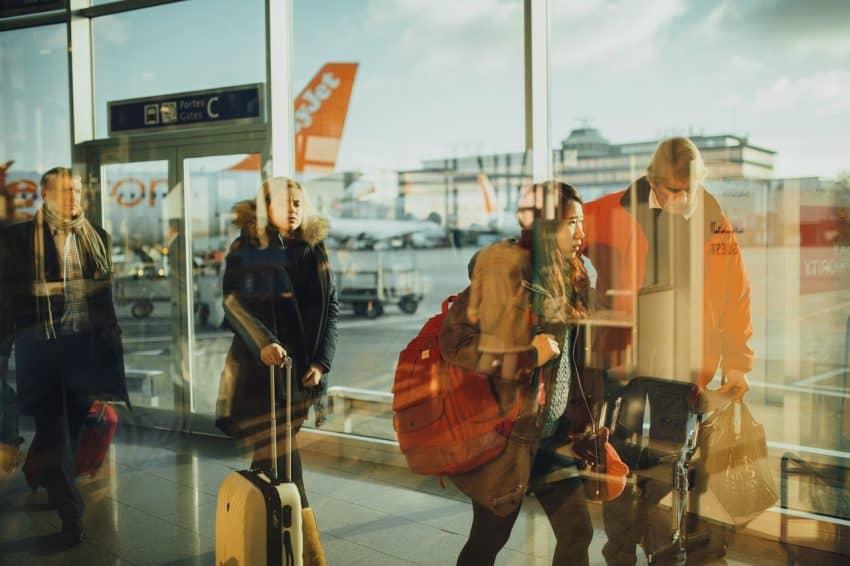 Pessoas caminhando com malas de viagem em um corredor de aeroporto.