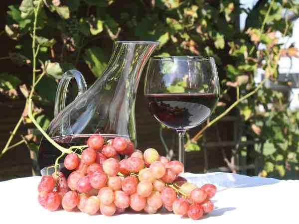 Na foto uma jarra com vinho ao lado de uma taça e uvas