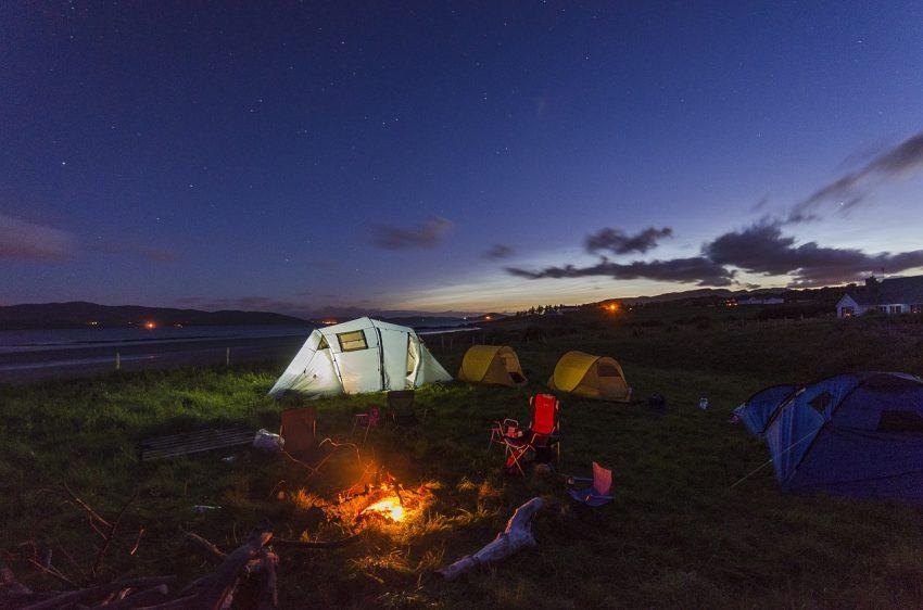 Anoitecer em um acampamento com uma fogueira e barracas em destaque.