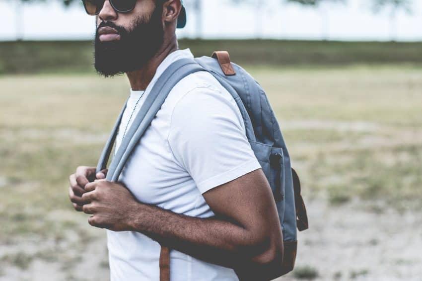 Homem carregando mochila jeans nas costas.