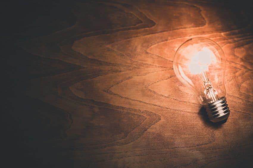 Imagem mostra lâmpada acesa sobre mesa.