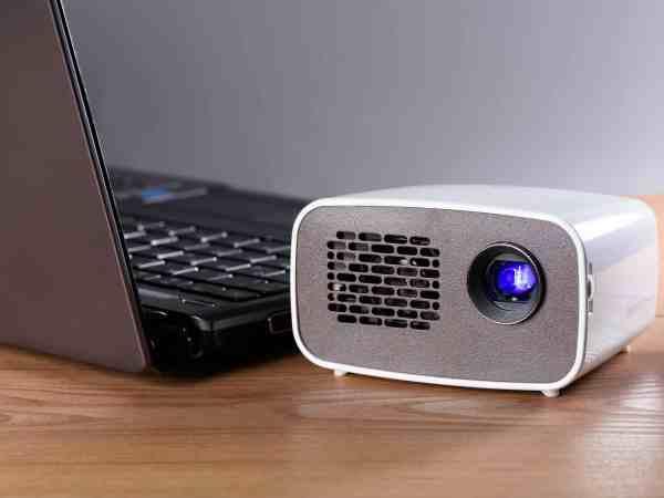 Imagem de um mini projetor junto a um computador.