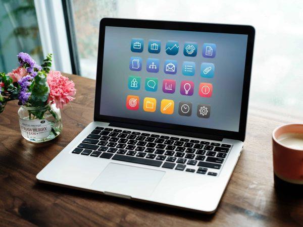 Imagem de um notebook em uma mesa com um vaso de flor ao lado