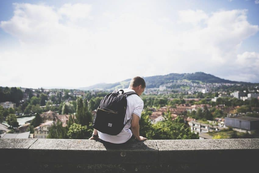 Garoto com mochila preta nas costas sentado no muro.