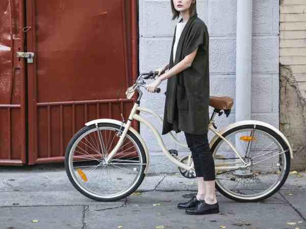 Mulher segurando bicicleta feminina retrô.