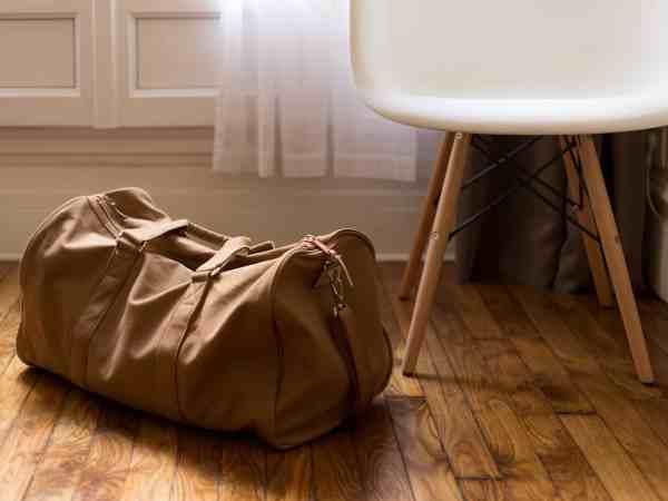 Bolsa de viagem marrom sobre piso em madeira ao lado de cadeira.
