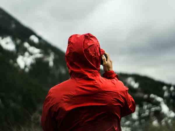 Imagem de pessoa com capa de chuva vermelha. tirando foto de paisagem chuvosa.