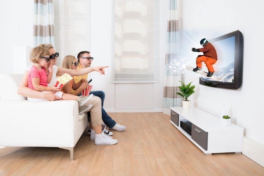 Imagem de uma família reunida no sofá vendo imagem em 3D na Smart TV.