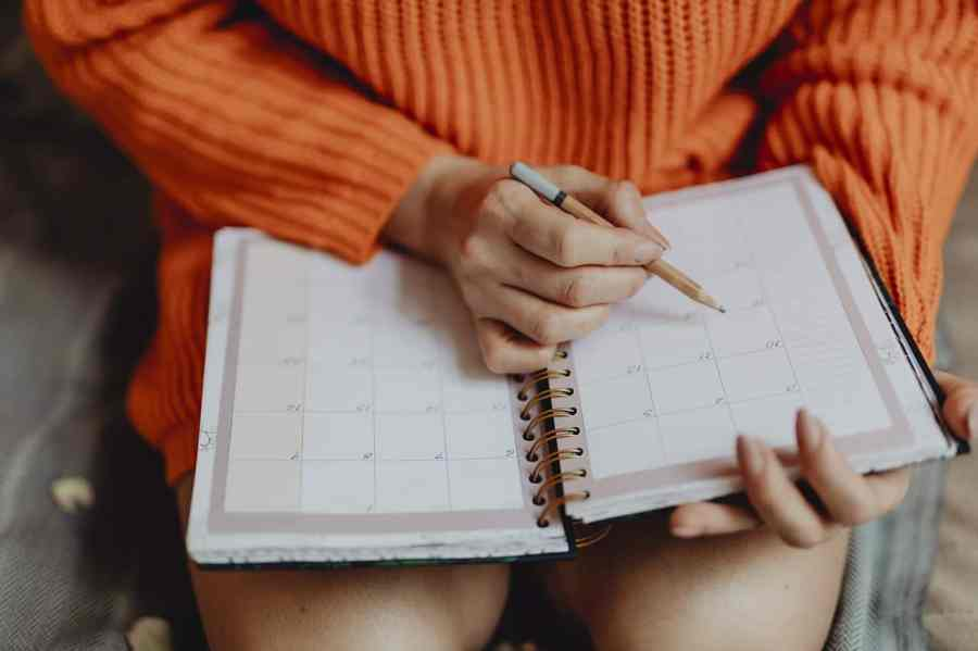 Imagem de uma mulher escrevendo em uma agenda do tipo mensal.