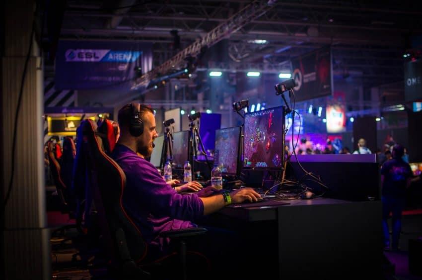 Imagem mostra um homem em frente a um monitor jogando em um PC gamer.