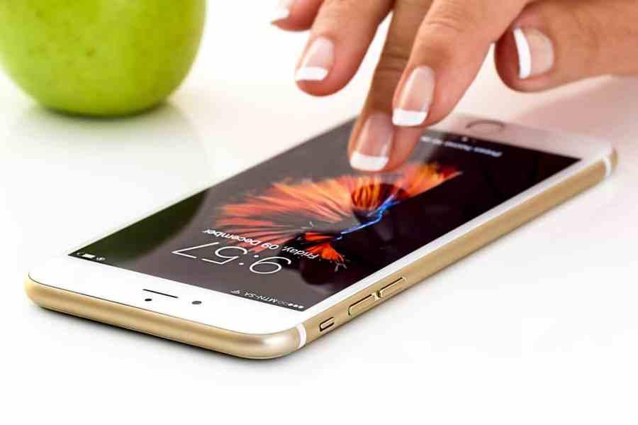 Imagem mostra uma mão feminina mexendo em um celular.