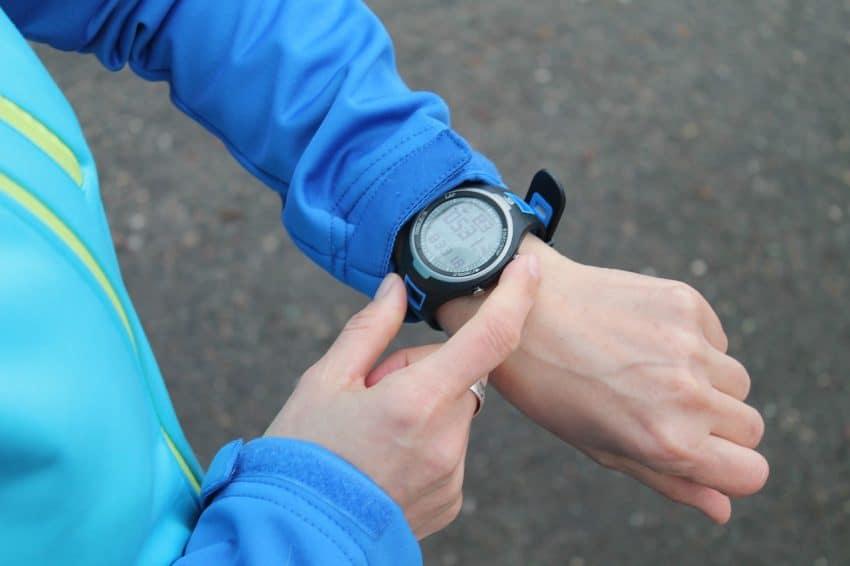 Imagem de uma mulher mexendo em seu relógio com monitor cardíaco.