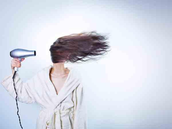 Mulher de roupão segurando um secador na altura de seus cabelos. Os cabelos estão voando horizontalmente.