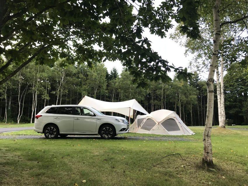 Imagem de uma tenda ao lado de uma barraca de camping e um carro estacionado em frente.
