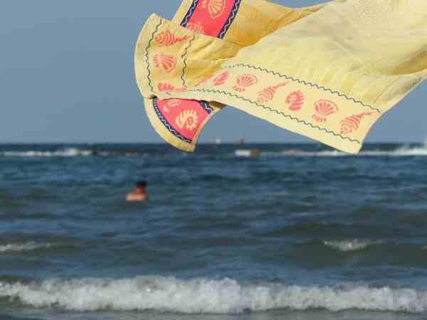 Toalha de praia perto do mar ao vento.