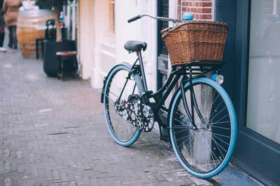 Bicicleta vintage apoiada na parede da rua.