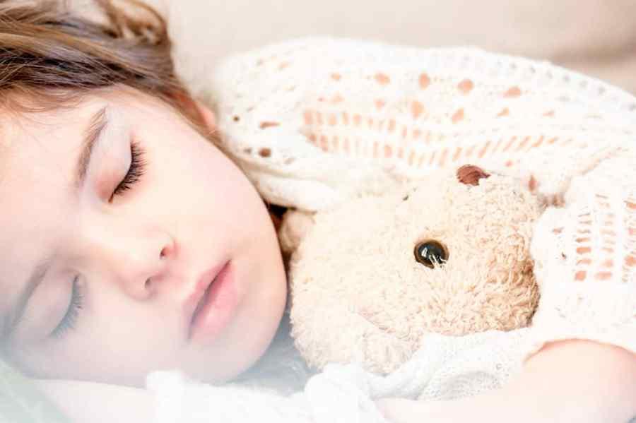 Imagem de criança dormindo abraçada a ursinho de pelúcia.