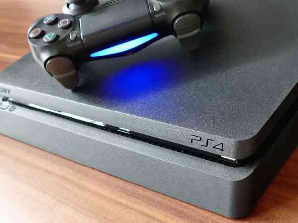 Imagem mostra um console e controle de PlayStation 4 sobre uma mesa de madeira.