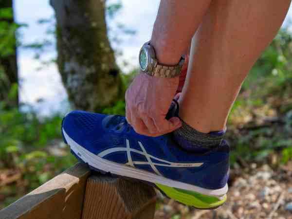 Pessoa não identificada amarrando um tênis azul. Ao fundo, há árvores e natureza.