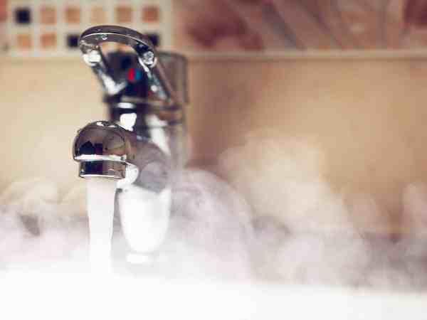 Imagem de torneira elétrica saindo água quente.
