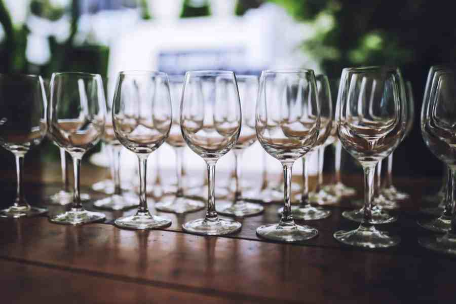 Foto de várias taças de vinho vazias em uma mesa de madeira.
