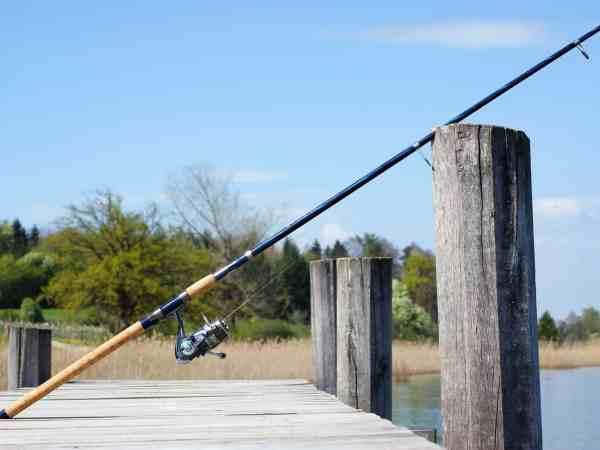 Imagem mostra uma vara de pesca sobre um píer.